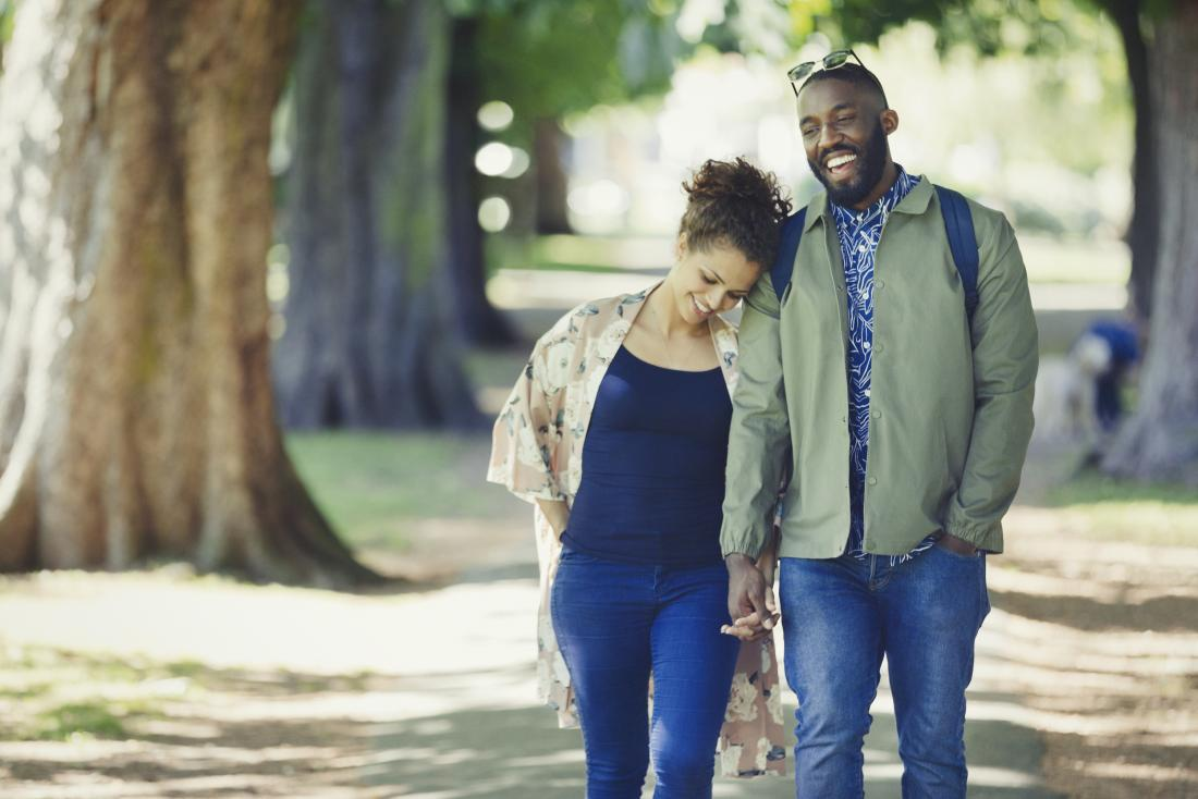 Loving couple holding hands and walking in park