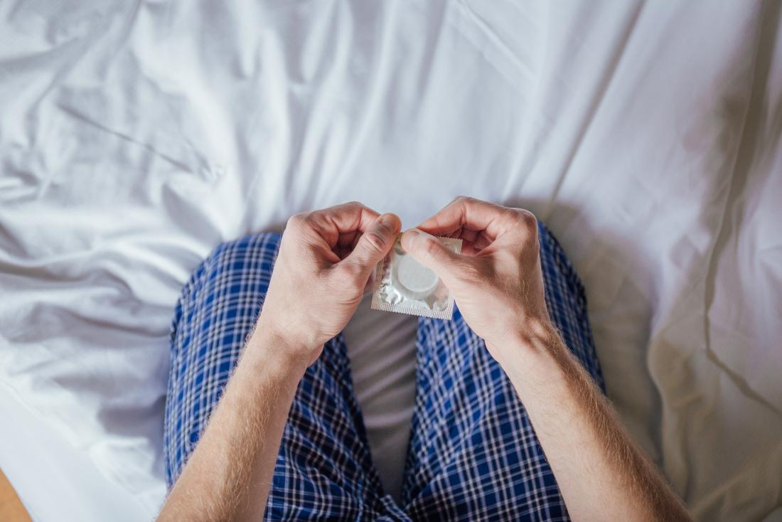 man on bed holding condom in packet