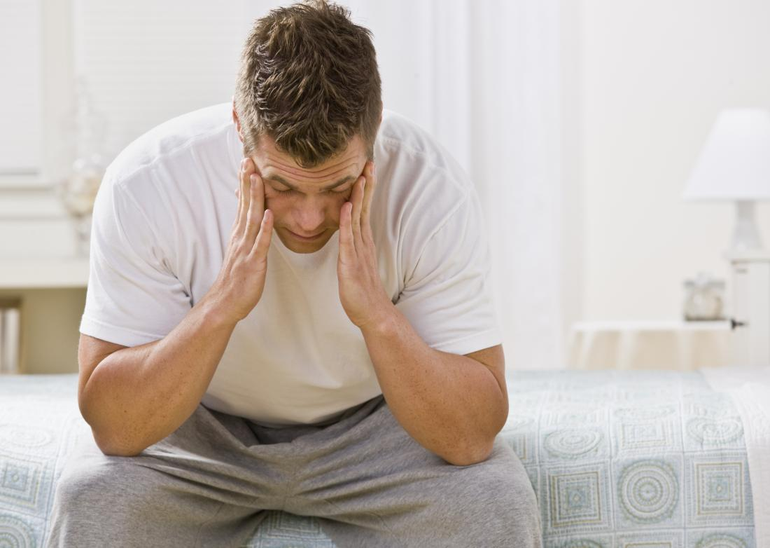 worried young man sitting on bed